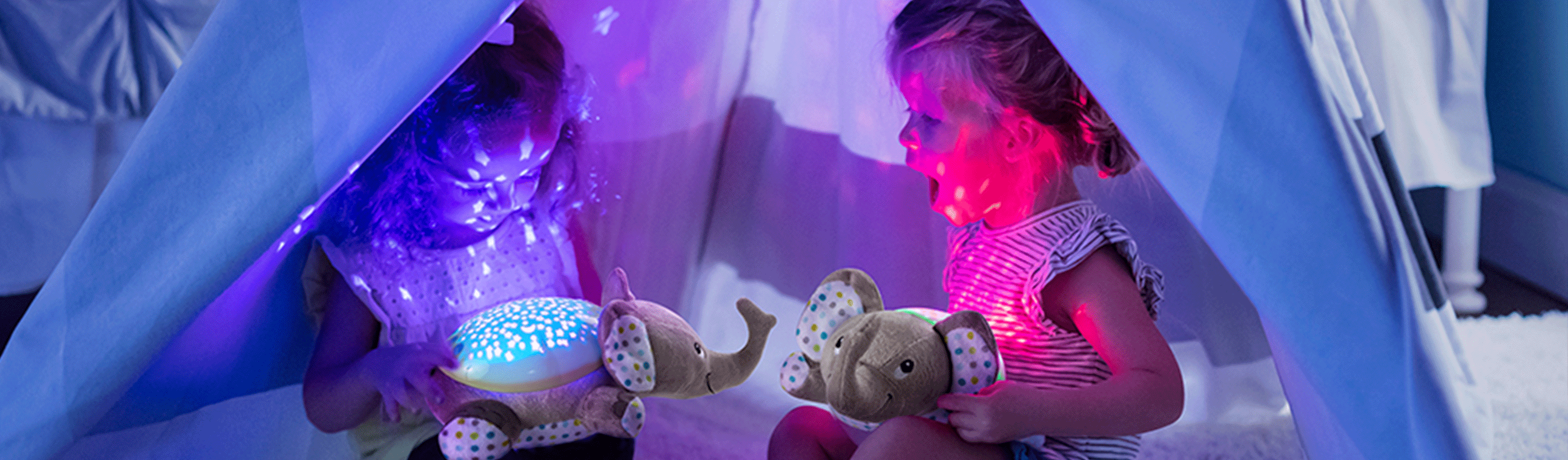 Two toddlers sit in a tent with their Summer Gray Elephant Soothers lighting up the tent and their faces.