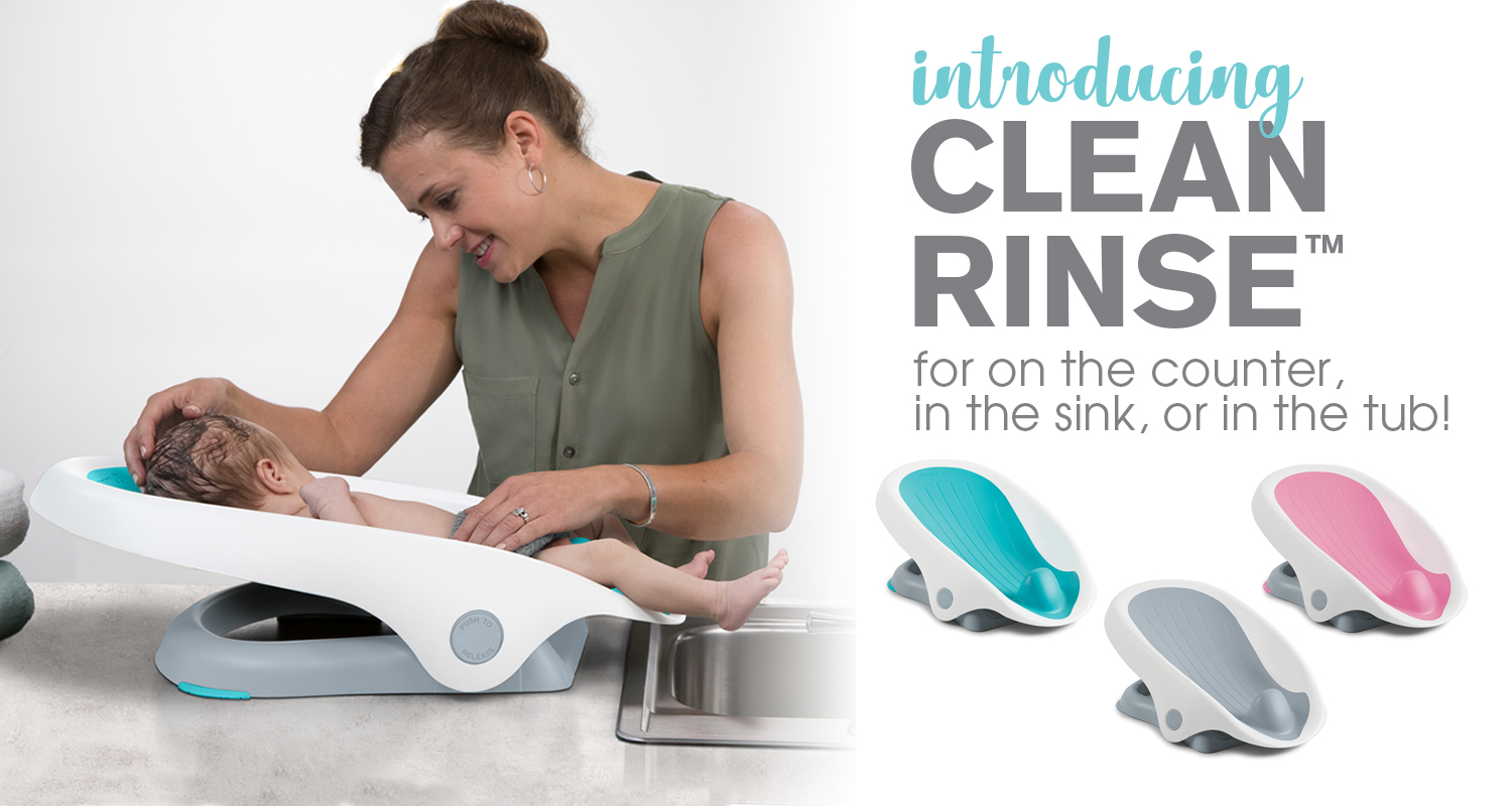 "Mother soothes baby in their Summer Clean Rinse Baby Bather. Text overlay says ""Introducing Clean Rinse. For on the counter, in the sink, or in the tub!""."