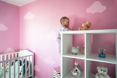 1 year old baby girl seems to be climbing shelving in pink nursery (image is photoshopped)