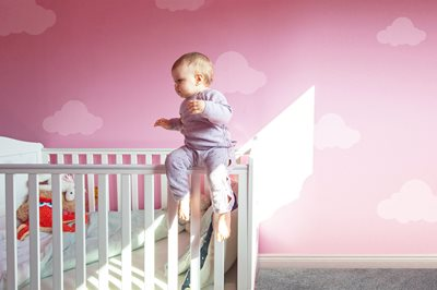 1 year old baby girl sits on white crib ledge in pink nursery (image is photoshopped)